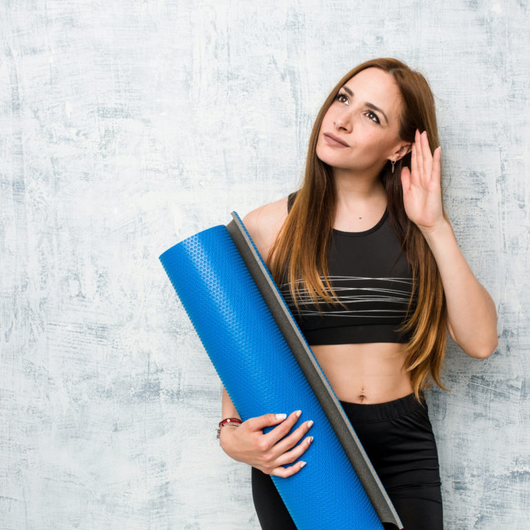 Young caucasian sportswoman holding a mat trying to listening a gossip.